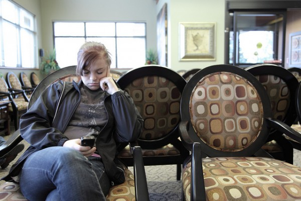 Teen girl texting in hospital waiting room