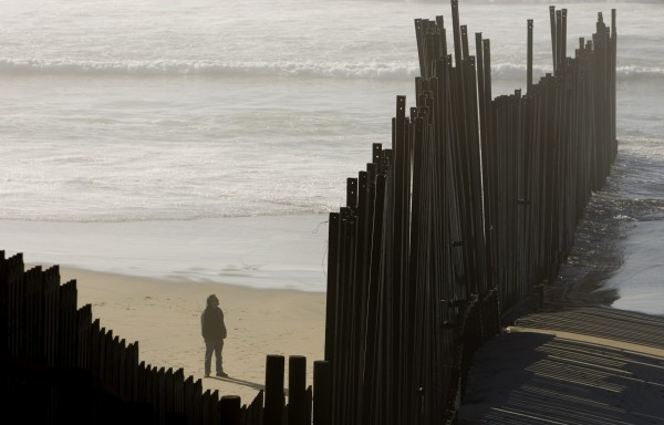 Man in Mexico looks at damaged border fence separating the US and Mexico in San Diego