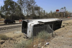 A tour bus ferrying passengers to a California casino lies on its side between a freeway and railroad tracks after it crashed in Irwindale