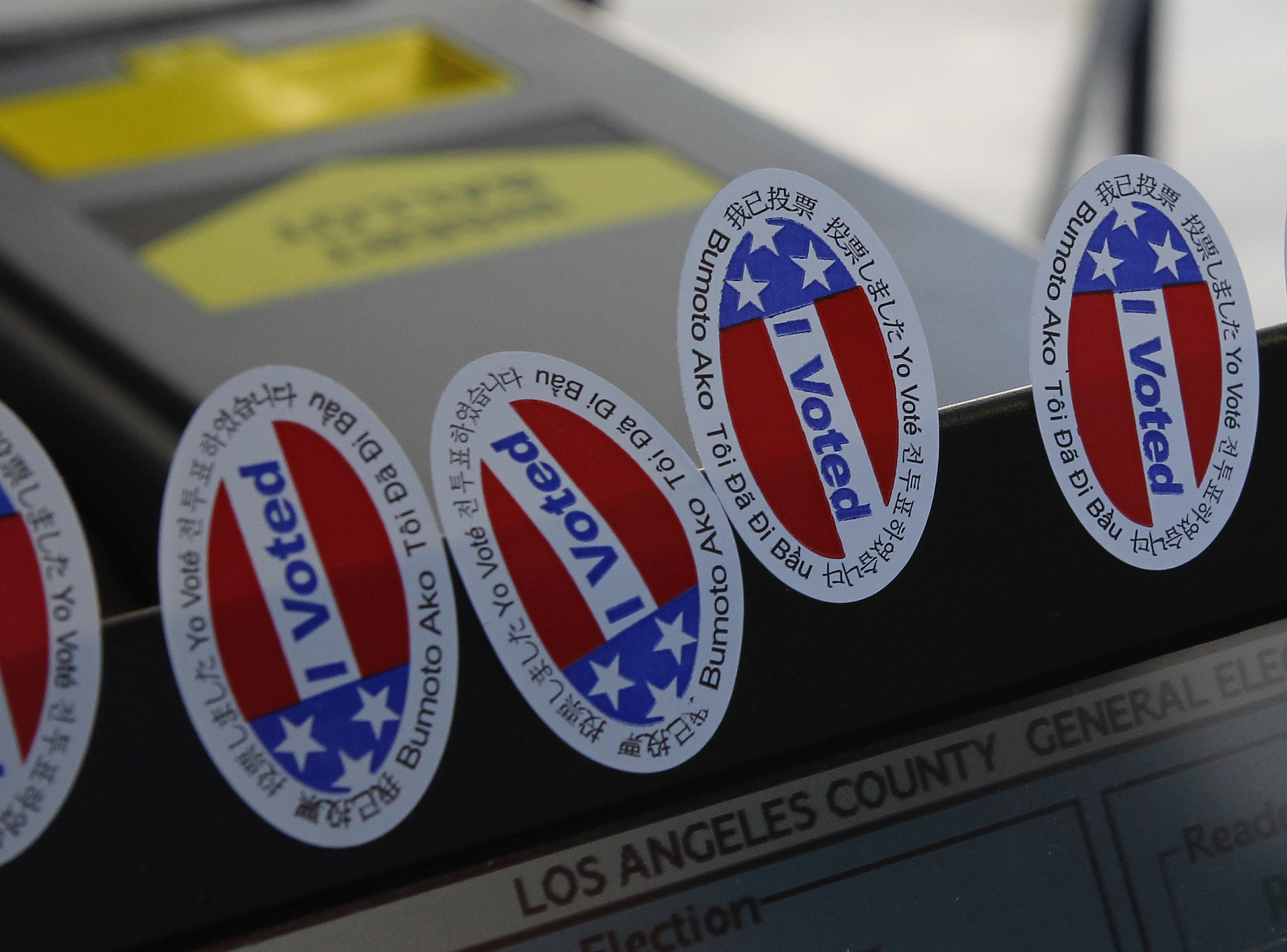 """Stickers stating """"I Voted"""" in several languages are affixed to a ballot intake machine at a polling station during the U.S. presidential election in Los Angeles"""