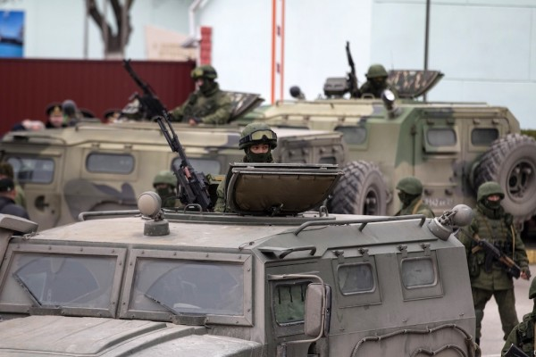 Armed servicemen stand in Russian army vehicles outside a Ukrainian border guard post in the Crimean town of Balaclava