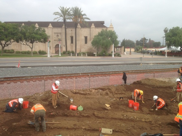 Workers excavating a historic water system in front of railroad tracks and the Mission San Gabriel