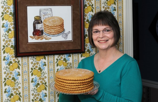 Jill Sauceman with her traditional dried apple stack cake. She inherited the recipe from her grandmother, Nevada Parker Derting, who lived in Scott County, Virginia. The watercolor painting of the stack cake on the wall was done by Nancy Jane Earnest.