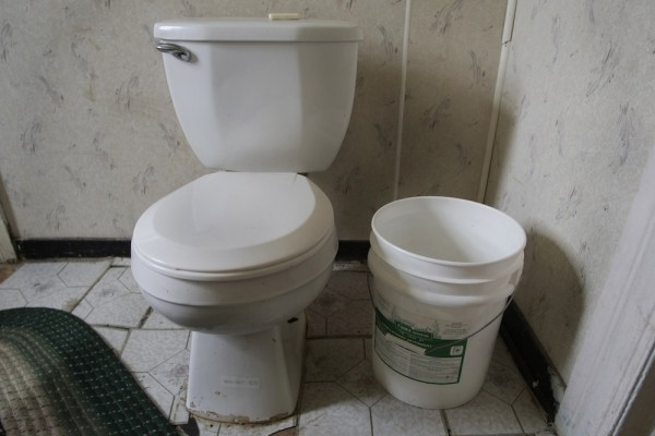 The toilet in Aaron Barkley and Gloria Irizarry's home and the bucket of water that is used to flush.