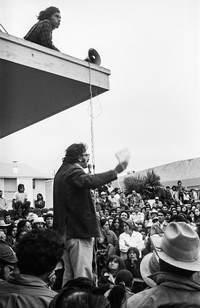 UFW organizer Marshall Ganz addresses farmworkers at a meeting in the yard of the Salinas union office, 1975