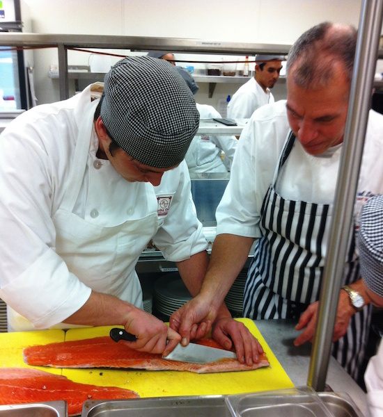 Chef Paul Lee, CEC, instructs student Chase Ewing in manufacturing a salmon