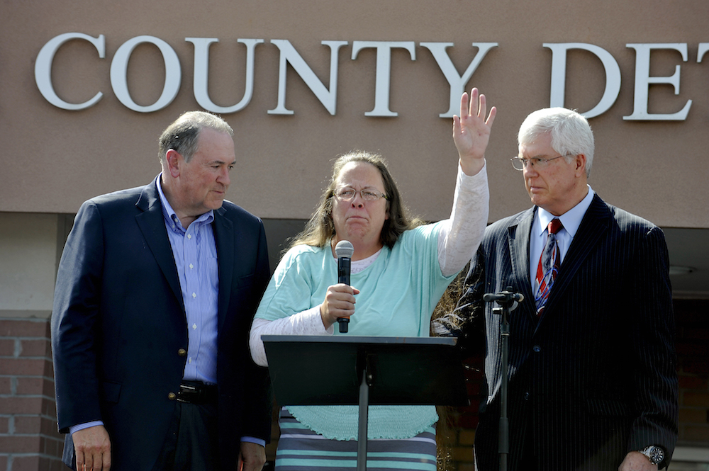 """Kim Davis, flanked by Republic presidential candidate Mike Huckabee (L) and and Attorney Mathew Staver (R) speaks to her supporters after walking out of jail in Grayson, Kentucky September 8, 2015. U.S. District Judge David Bunning ordered her release after six days in jail, saying she """"shall not interfere in any way, directly or indirectly, with the efforts of her deputy clerks to issue marriage licenses to all legally eligible couples.""""  REUTERS/Chris Tilley - RTX1RPQ3"""