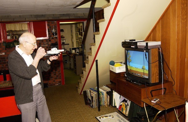 Baer playing a videogame he invented; his basement workshop is in the background. Courtesy of Smithsonian National Museum of American History.
