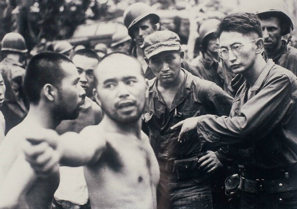 Harry (right), an officer in the U.S. Army, interrogates a Japanese POW in Aitape, New Guinea, in April 1944.