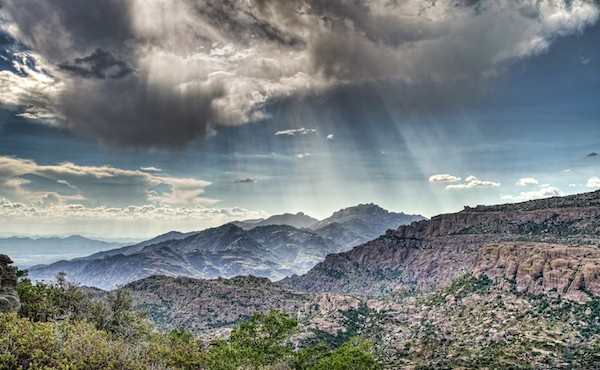 Rays of light during monsoon rains over the Catalina Mountains outside Tucson, Arizona.