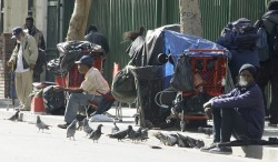 Men and their belongings sit and stand Just yards from where hundreds of the homeless and needy are being served Thanksgiving dinner, at the Los Angeles Mission in the city's Skid Row district Wednesday, Nov. 24, 2010.  (AP Photo/Reed Sasxon)