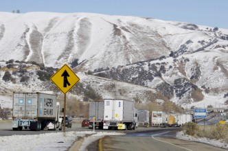 The Tehachapi Mountains have a blanket of snow as hundreds of vehicles, many of them stopped overnight, move along Interstate 5 near Gorman, Calif., shortly after it reopened after a snowstorm closed California's main north-south artery in the Tehachapis Tuesday, Dec. 8, 2009.  (AP Photo/Reed Saxon)