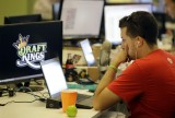 FILE - In this Sept. 9, 2015 file photo, Devlin D'Zmura, a tending news manager at DraftKings, a daily fantasy sports company, works on his laptop at the company's offices in Boston.  Customers of the two biggest daily fantasy sports websites have filed at least four lawsuits against the sites in Oct. 2015, following cheating allegations and a probe into the largely-unregulated multi-billion dollar industry. In court papers, the customers accused the DraftKings and FanDuel sites of cheating, and argued they never would have played had they known employees with insider knowledge were playing on rival sites.  (AP Photo/Stephan Savoia)