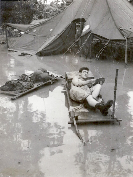 A soldier enjoys a paperback in a flooded camp.