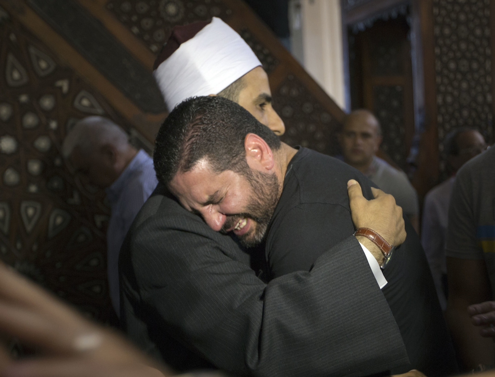 FILE - In this Friday, May 20, 2016 file photo, The Imam of al Thawrah Mosque, Samir Abdel Bary, gives condolences to Tarek Abu Laban, center, who lost four relatives, all victims of EgyptAir plane crash, following prayers for the dead, at al Thawrah Mosque in Cairo, Egypt. Human remains retrieved from the crash site of EgyptAir Flight 804 suggest there was an explosion on board that may have brought down the aircraft in the east Mediterranean, a senior Egyptian forensics official said on Tuesday, May 24, 2016. (AP Photo/Amr Nabil, File)