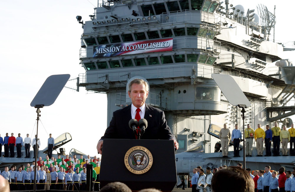 "** FILE ** President Bush declares the end of major combat in Iraq as he speaks aboard the aircraft carrier USS Abraham Lincoln off the California coast, in this May 1, 2003 file photo. Democratic congressional leaders on Tuesday, May 1, 2007 sent Iraq legislation setting timetables for U.S. troop withdrawals to President George W. Bush and a certain veto.  On the fourth anniversary of the president's ""Mission Accomplished"" speech, Senate Majority Democratic Leader Harry Reid said that Bush ""has put our troops in the middle of a civil war. A change of course is needed.""  (AP Photo/J. Scott Applewhite)"