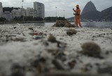 A clean workers removes the trash over the sand of Botafogo beach next to the Sugar Loaf mountain and the Guanabara Bay in Rio de Janeiro, Brazil, Saturday, July 30, 2016. (AP Photo/Leo Correa)
