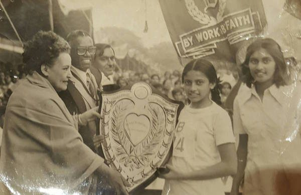 The author's sister, Karen Mayer, receiving the best all-round athlete award with their father (in glasses) looking on. Circa 1980.