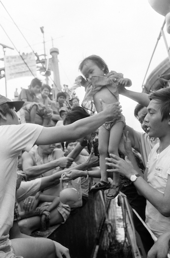 Fellow refugees transfer a Vietnamese child onto a Coast Guard boat in Manila, Philippines on Jan. 8, 1979.