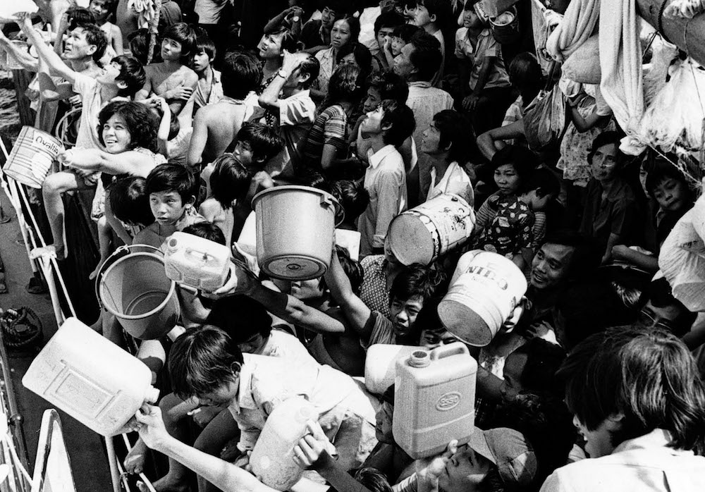 "Vietnamese ""boat people"" aboard the refugee ship ""Tung An"" hold out pails and cans to crewmen of a Philippine Navy ship that docked alongside the vessel February 21,1979 with a fresh supply of drinking water. The refugees have been stranded aboard the Tung An in Manila Bay for eight weeks. (AP Photo)"