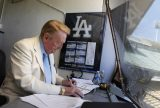 Vin Scully works in his booth at Dodger Stadium in Los Angeles, Sunday, Aug. 22, 2010. cully will return to the broadcast booth to call Los Angeles Dodgers games next year for his 62nd season. The team said Sunday that the 82-year-old Hall-of-Famer will call all home games and road games against National League West opponents. (AP Photo/Jae C. Hong)
