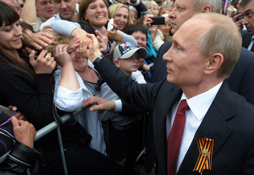 "Russian President Vladimir Putin, center, is greeted by people in Sevastopol where he attends celebrations marking  the Victory Day, Crimea, Friday, May 9, 2014. President Vladimir Putin hailed the return of Crimea to Russia as the restoration of ""historic justice"" before a jubilant, welcoming crowd Friday on the holiday that Russians hold dearest. Putin's visit to the Crimean port of Sevastopol, was strongly criticized by both NATO and Ukraine's Foreign Ministry. (AP Photo/RIA-Novosti, Alexei Druzhinin, Presidential Press Service)"