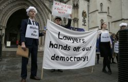 "Supporters of the pro-democracy group ""Invoke Article 50 Now!"" hold a banner as pro-EU membership supporters hold EU flags on the first day of Gina Miller's, a founder of investment management group SCM Private, lawsuit at the High Court, in London, Thursday, Oct. 13, 2016. The financial entrepreneur's landmark lawsuit begins with a simple question: can Prime Minister Theresa May's government invoke Article 50 and trigger Britain's exit from the European Union without an act of Parliament? .(AP Photo/Alastair Grant)"