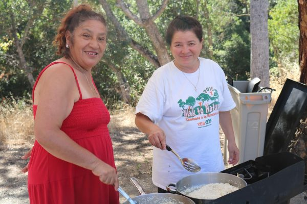 Navigators Maria and Guadalupe cooking outdoors.