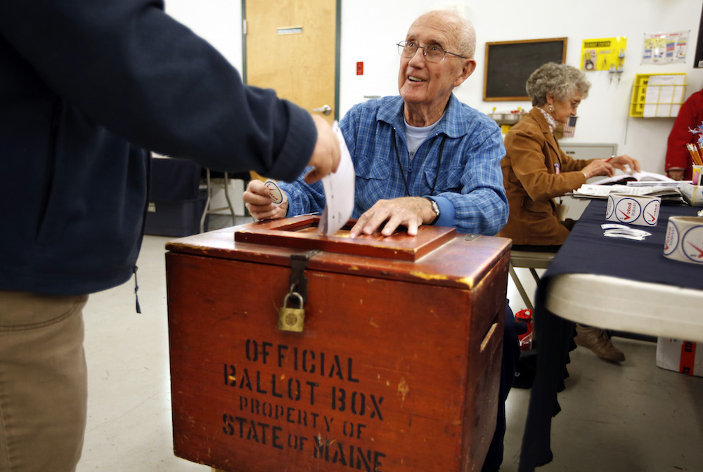 Daniel Mulcahey mans the ballot box as a resident casts his vote in an old-fashioned wooden ballot box at the polling place in Brooks, Maine, on Election Day, Tuesday, Nov. 4, 2014.  (AP Photo/Robert F. Bukaty)
