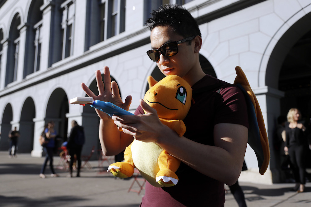 """Tim C., who did not want to give his last name, searches for Pokemon during a gathering of """"Pokemon Go"""" players Wednesday, July 20, 2016, in San Francisco.(AP Photo/Marcio Jose Sanchez)"""