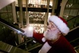 ** ADVANCE FOR MONDAY, DEC. 12 ** Jim Roetheli, one Marshall Field's Santas, takes an escalator up through one of the stores atriums level Wednesday, Nov. 30, 2005, in downtown Chicago.  For many Field's is synonymous with Christmas in Chicago and this will be the last season to celebrate it under the venerable department store's name. By next season the store will be renamed Macy's, which is decidely New York. (AP Photo/Charles Rex Arbogast)