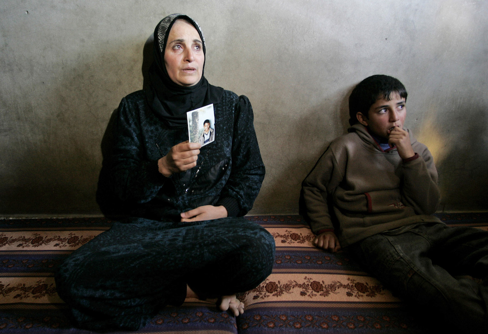 Ibtissam Laghwan, left, the mother of Luay Laghwan, one of two suicide bombers who carried out an attack in the Israeli town of Dimona, holds a picture of him as a child at the family house in Gaza City, Monday, Feb. 4, 2008. A Palestinian suicide bomber on Monday blew himself up in Dimona, the southern town that houses Israel's secretive nuclear reactor, killing an Israeli woman and wounding seven other people, Israeli authorities said. Police said they killed a second attacker before he had a chance to detonate his explosives belt. (AP Photo/Hatem Moussa)