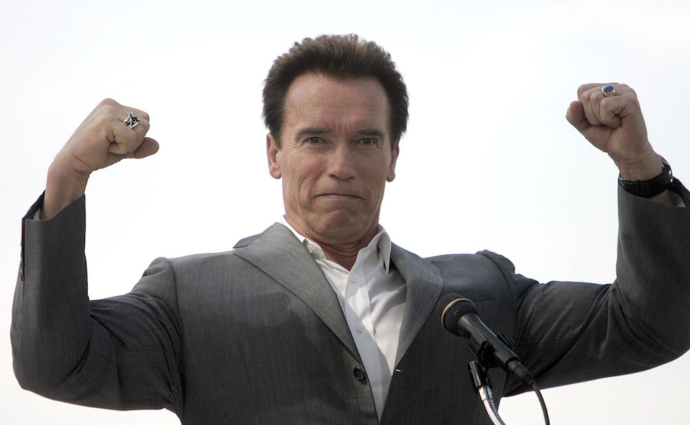 California Governor Arnold Schwarzenegger flexes during a speech for the California Prison Industry Authority apprenticeship training program graduation at the California Institution for Women in Chino, Calif., March 6, 2008.  The program trains female inmates in construction skills. (AP/The Press-Enterprise/Silvia Flores) **MANDATORY CREDIT**NO SALES, MAGS OUT**