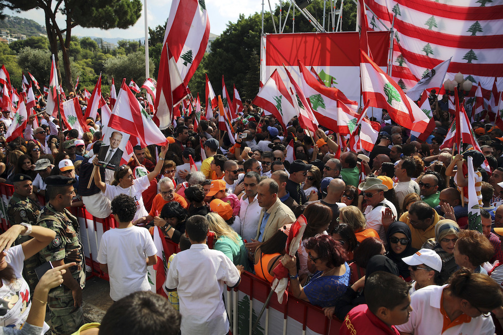 Supporters of Lebanon's newly elected president, Michel Aoun, gather as they hold Lebanese flags at the presidential palace in Baabda, east of Beirut, Lebanon, Sunday, Nov. 6, 2016 to celebrate Aoun's election. Aoun has vowed to uproot corruption and strive for nation-building in the deeply divided country. (AP Photo/Bilal Hussein)