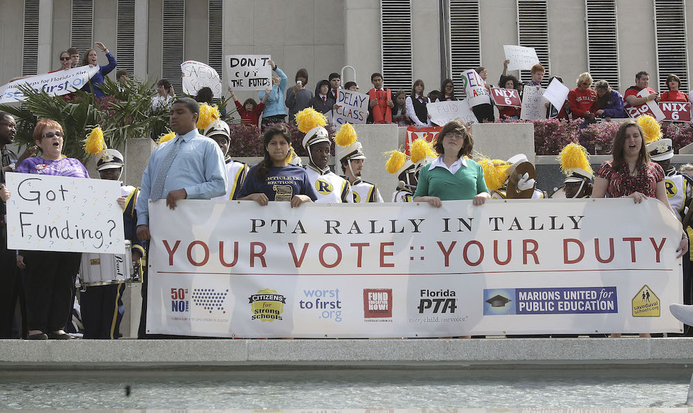 The Parents Teachers Association holds a rally for public education dollars, Thursday, March 25, 2010, in Tallahassee, Fla.  At left is former Representative Curtis Richardson who was at the rally in support.(AP Photo/Phil Coale)