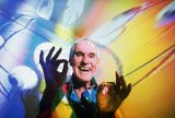 Timothy Leary, the former LSD experimentor turned computerized hallucination designer, in his Beverly Hills home in 1992 with video images from his show projected over him. Leary, who suffered from cancer, died in 1996 at 75. Photo courtesy of Associated Press.