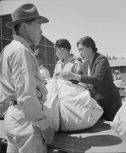 Baggage is inspected as Japanese American families arrive in Turlock, California, en route to War Relocation Authority centers. Photo by Dorothea Lange, courtesy of the National Archives and Records Administration/Densho Digital Reposity.