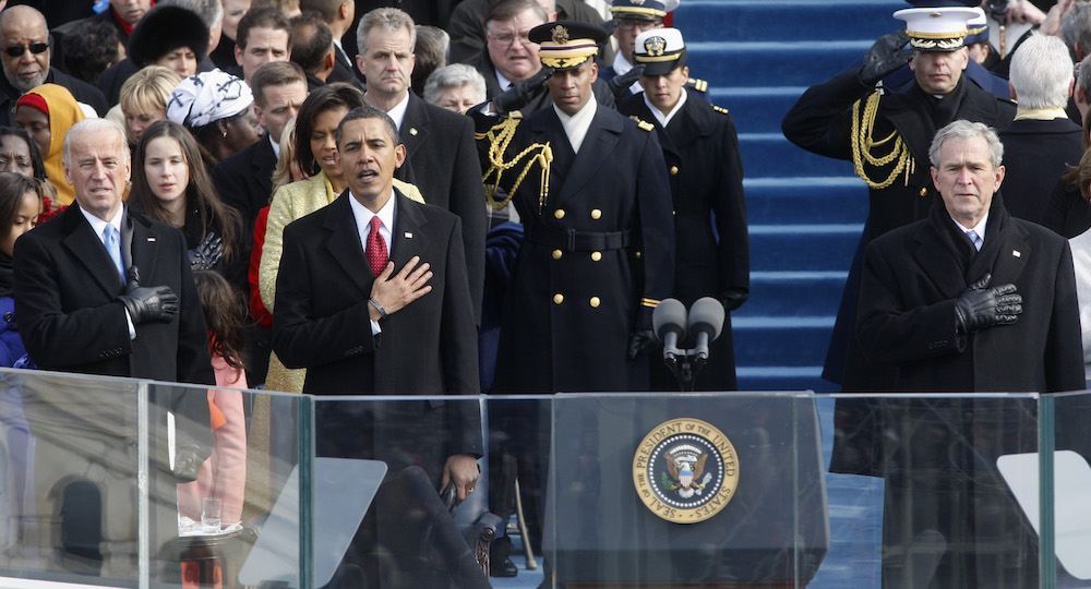 Vice President Joe Biden, left, President Barack Obama, and former President George W. Bush, right, sing the national anthem at the end of the swearing-in ceremonies at the U.S. Capitol in Washington, Jan. 20, 2009.  Photo by Ron Edmonds/Associated Press.