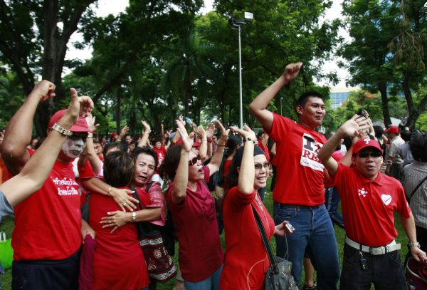 Members of the United Front for Democracy against Dictatorship (UDD) or Red Shirt cheer for news report of the by-election at Lumpini park in Bangkok, Thailand, July 2010. About 200 UDD members took part in the gathering to show their unity and to defy the country's security act. Photo by Apichart Weerawong/Associated Press.