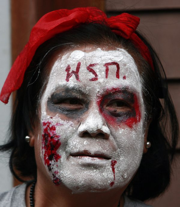 A member of the UDD or Red Shirt puts makeup on her face as a dead person at Lumpini park in Bangkok, Thailand, July 2010. Photo by Apichart Weerawong/Associated Press.