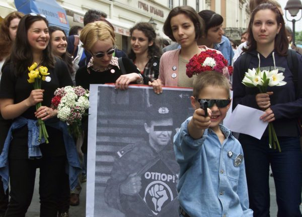 An unidentified Belgrade boy holds a plastic toy gun mocking police officers in Belgrade, Serbia, May 2000. Members of the pro-opposition student group Otpor, or Resistance, gave out flowers to policemen and appealed for their restraint in the worsening government crackdown on political opponents. Photo by Darko Vojinovic/Associated Press.