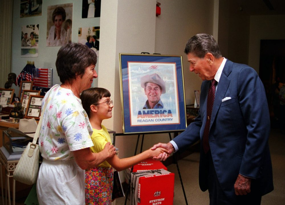 Former President Ronald Reagan, during a visit to the Ronald Reagan Presidential Library and Museum, shakes hands with 9-year-old Janine Hicks of San Diego, who was touring the museum with her grandmother, Lily Visniski of Thousand Oaks,  in 1997. Photo by Mike Guastella/Associated Press.