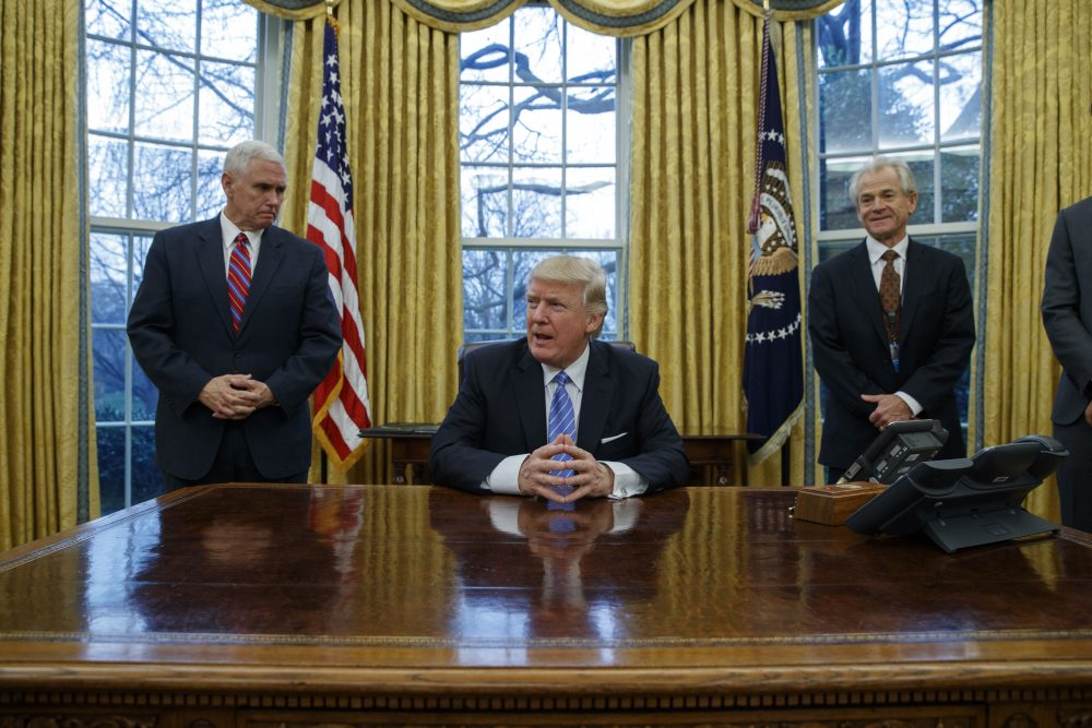 Vice President Mike Pence, left, and National Trade Council adviser Peter Navarro, right, wait for President Donald Trump to sign three executive orders, Monday, Jan. 23, 2017, in the Oval Office of the White House in Washington. Photo by Evan Vucci/Associated Press.