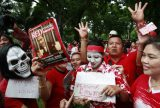 Members of the United Front for Democracy against Dictatorship (UDD) or Red Shirt put makeup on their faces at Lumpini park in Bangkok, Thailand, July 2010. About 200 UDD members took part in the gathering to show their unity and to defy the country's security act. Photo by Apichart Weerawong/Associated Press.