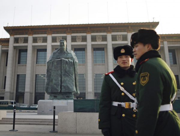 Chinese paramilitary policemen stand guard in front of a sculpture of the ancient philosopher Confucius on display near Tiananmen Square in Beijing, Jan. 2011. Photo by Andy Wong/Associated Press.