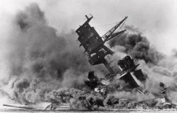 """Smoke rises from the battleship USS Arizona as it sinks during the Dec. 7, 1941 Japanese surprise attack on Pearl Harbor. The cyber age """"gray zone"""" makes it hard to determine what the cyber equivalent of such an attack would be. Photo by Associated Press."""