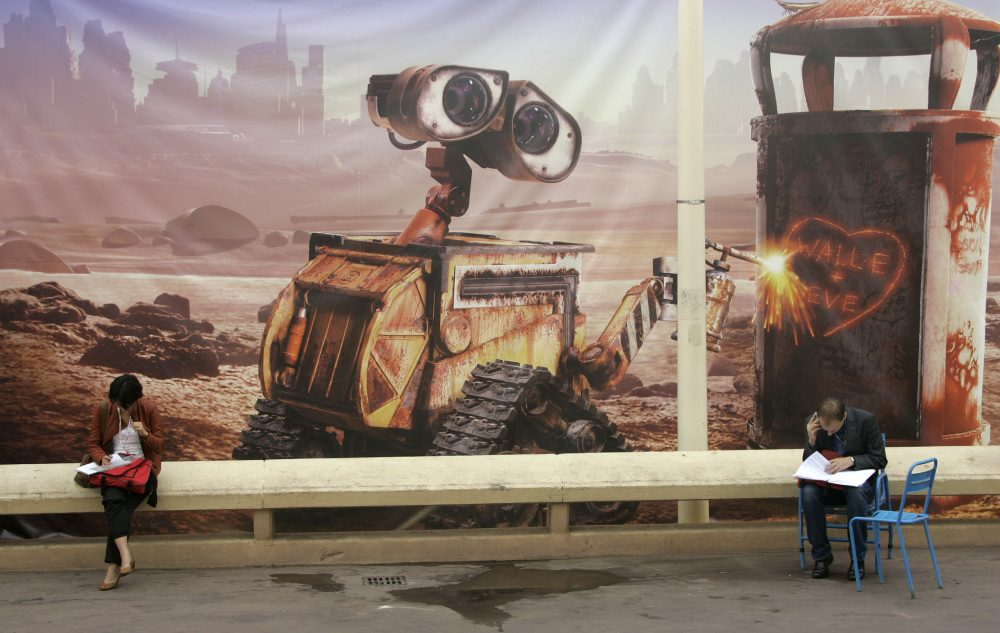 Visitors sit in front of a WALL-E poster at the 24th MIPCOM (International Film and Programme Market for TV, Video, Cable and Satellite) in Cannes, France, Oct. 2008. Photo by Lionel Cironneau/Associated Press.