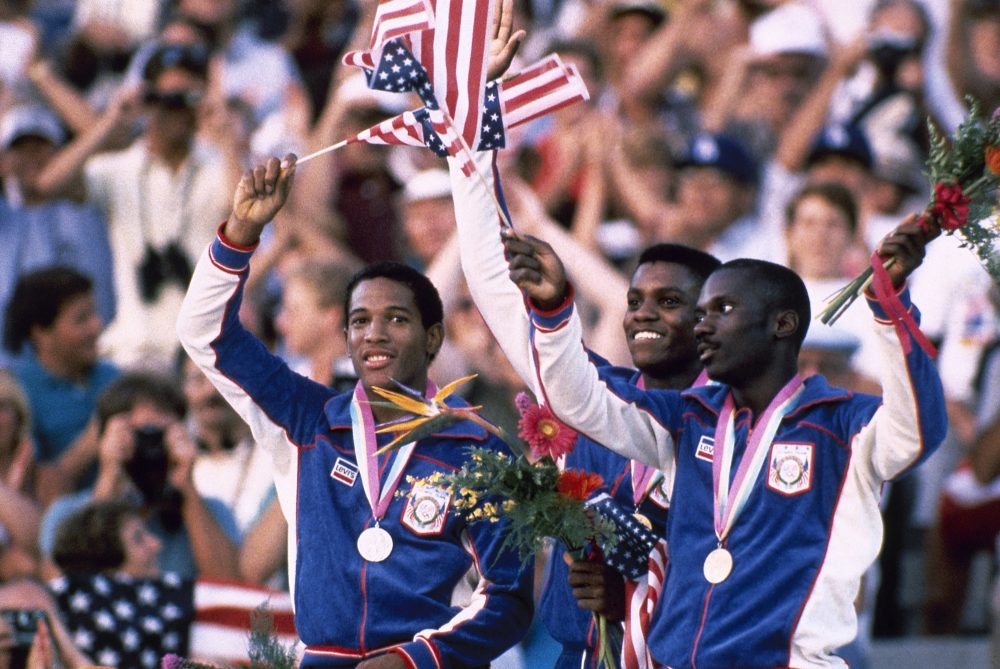 L-R: Silver medalist Kirk Baptiste (19.96 seconds); gold medal winner Carl Lewis (19.80); and Thomas Jefferson (20.26) who won bronze, wave American flags on the podium after the Men's 200 Meter race at the Summer Olympic Games in Los Angeles on Aug. 8, 1984. Photo by Associated Press.