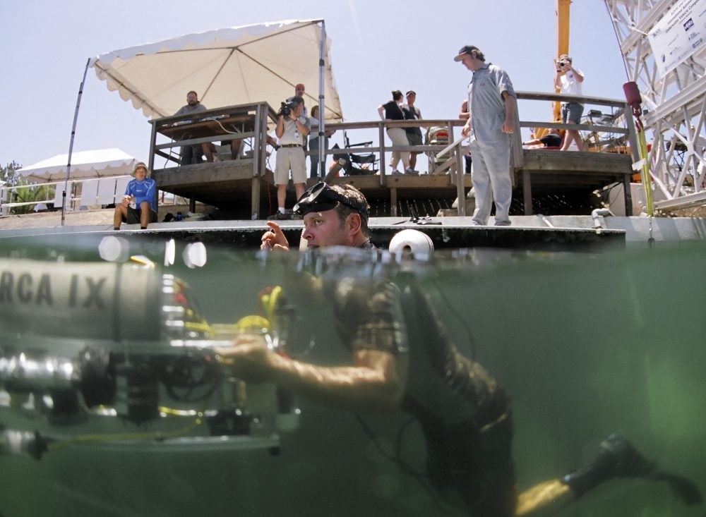 A diver from the U.S. Navy's Space and Naval Warfare Command pushes an underwater robot into its starting location at the International Autonomous Underwater competition in San Diego, Aug. 4, 2006. The confluence of a strong military presence and a robust entrepreneurial culture have produced a growing number of cybersecurity businesses. Photo by Chris Park/Associated Press.