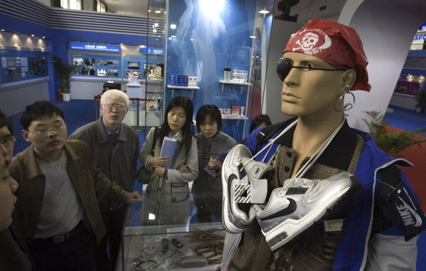 Visitors walk past a mannequin set up to show how individuals attempt to get past customs, smuggling counterfeit products in violation of intellectual property rights law during an exhibition in Beijing, April 17, 2006. Photo by Ng Han Guan/Associated Press.